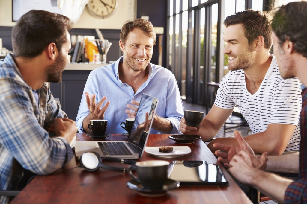 Group of men talking at a coffee shop