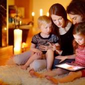 Happy family using tablet pc by a fireplace