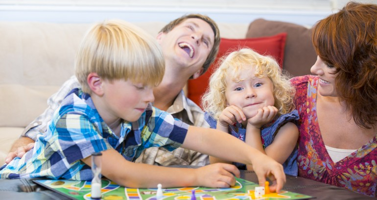 Family with two kids having fun playing board games