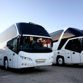 Two white coach busses on road at dusk