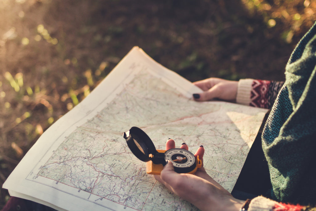 Traveler young woman searching direction with a compass on background of map in the forest