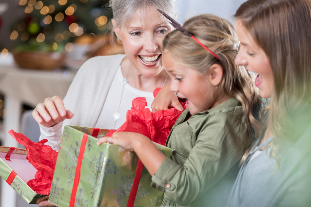 Excited girl is surprised while opening Christmas present