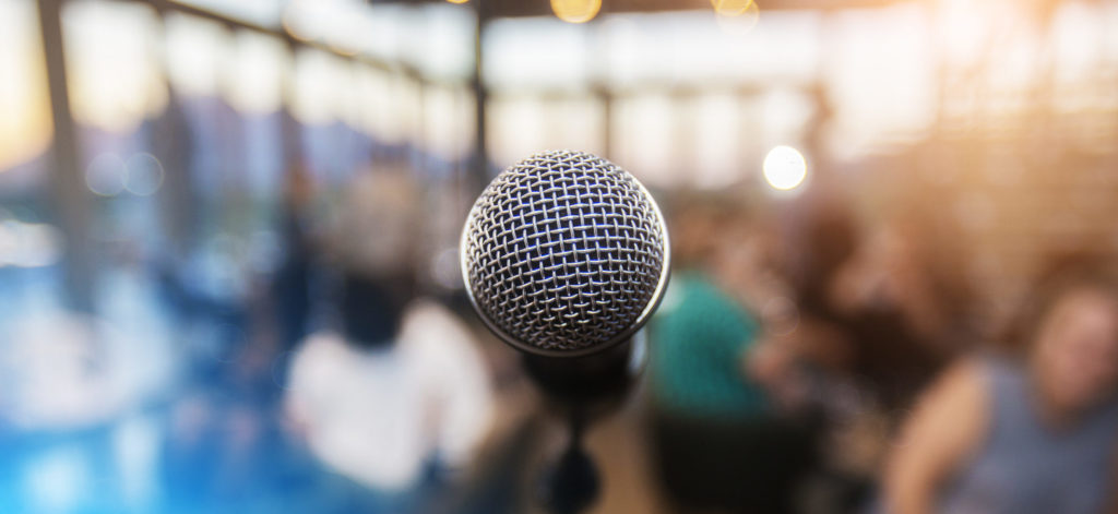 Microphone infront of an out of focus audience