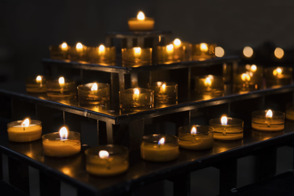 A collection of lit prayer candles against a dark backdrop