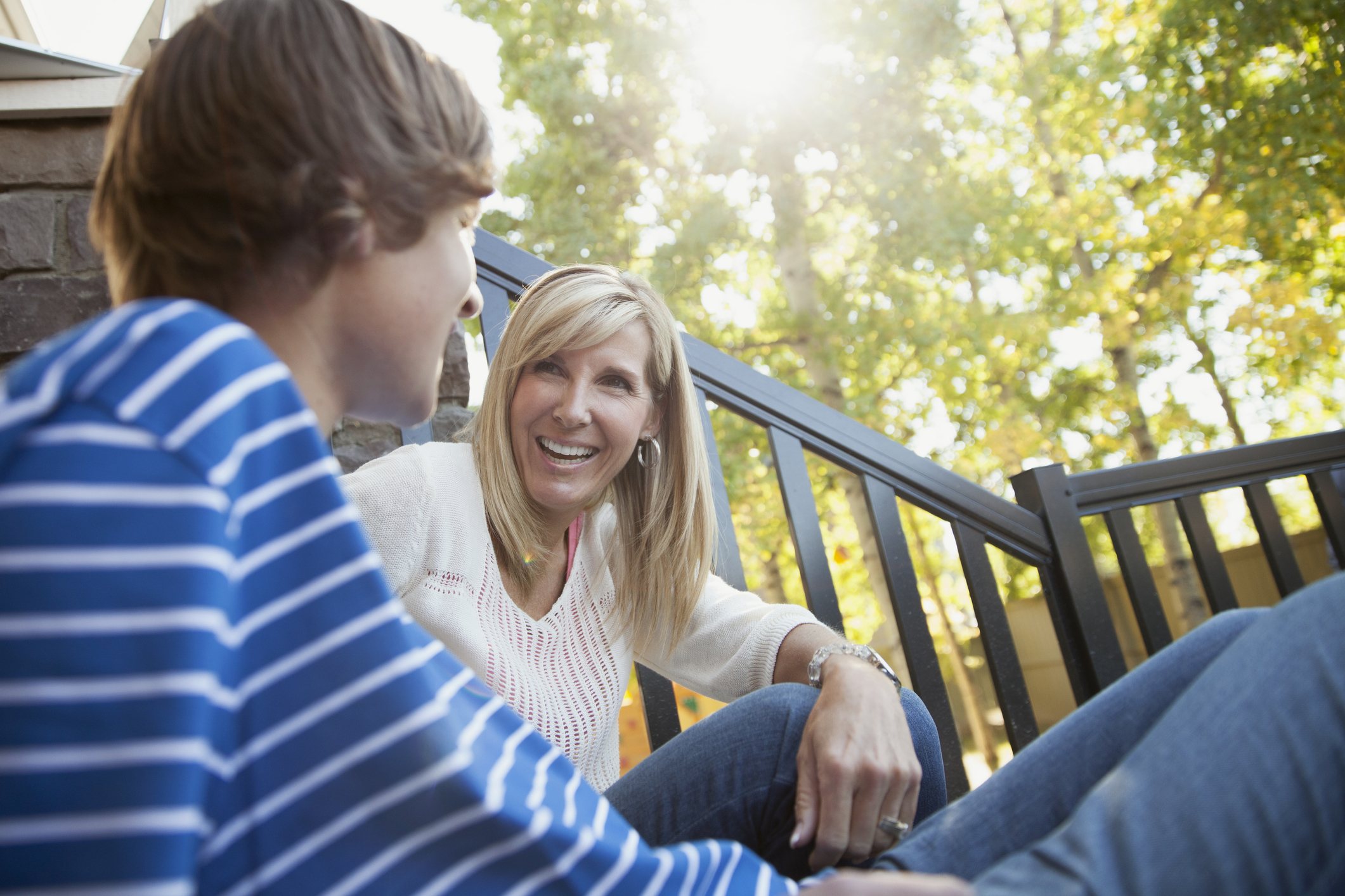 Happy mother looking at son while sitting together on front steps