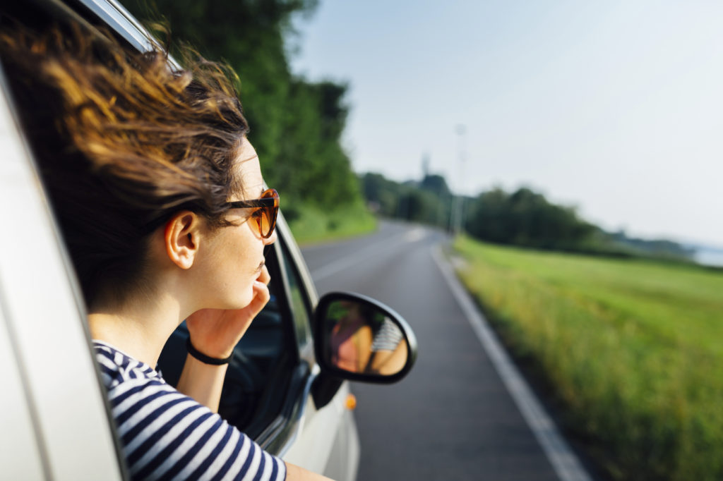 Wanderlust woman look at view traveling by car