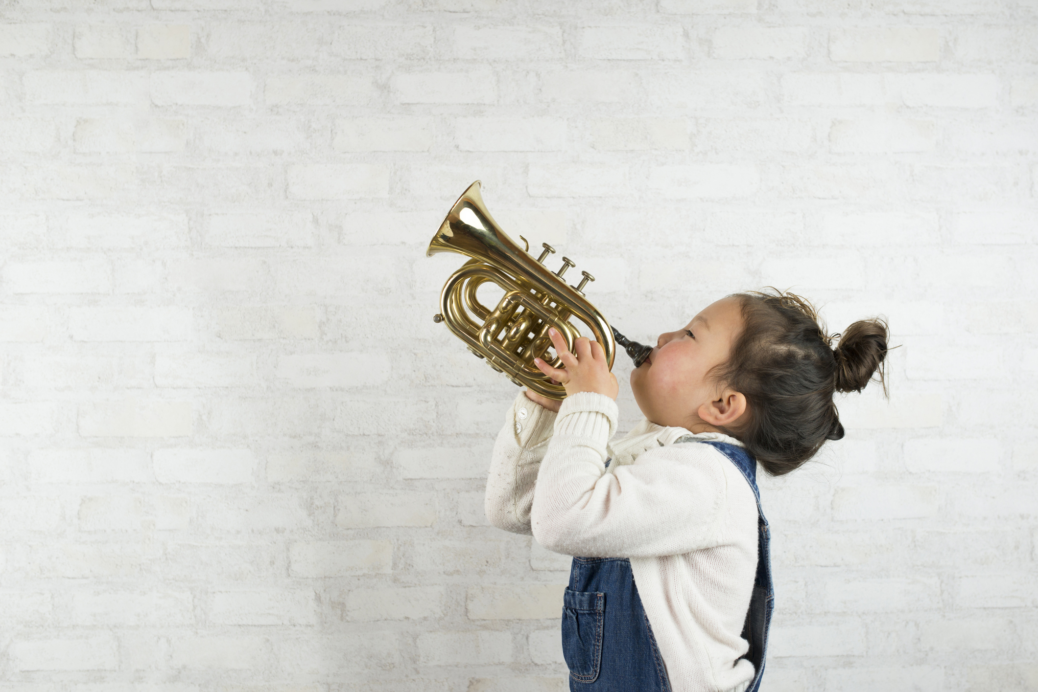 Little girl playing the trumpet