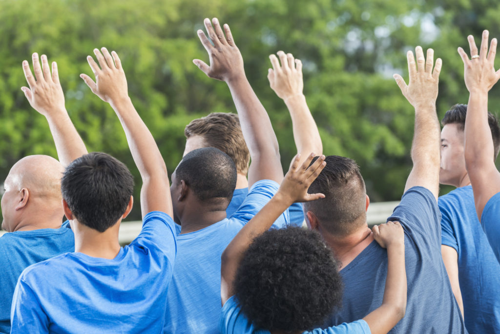 Rear view of a group of multi-ethnic men and boys wearing blue shirts, raising their hands. They are a group of volunteers working on a community service project.