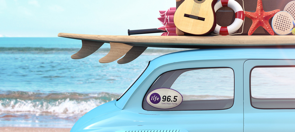 a surfboard and various other items atop a car parked next to the ocean