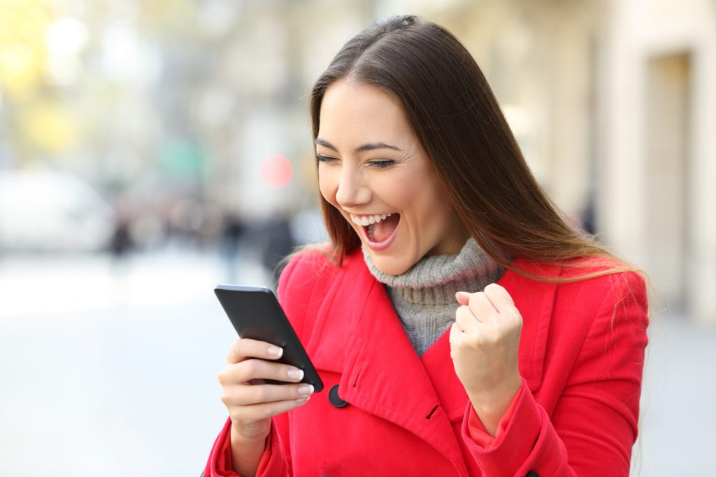 Portrait of an excited woman wearing a red coat winning on line outside on the street in winter