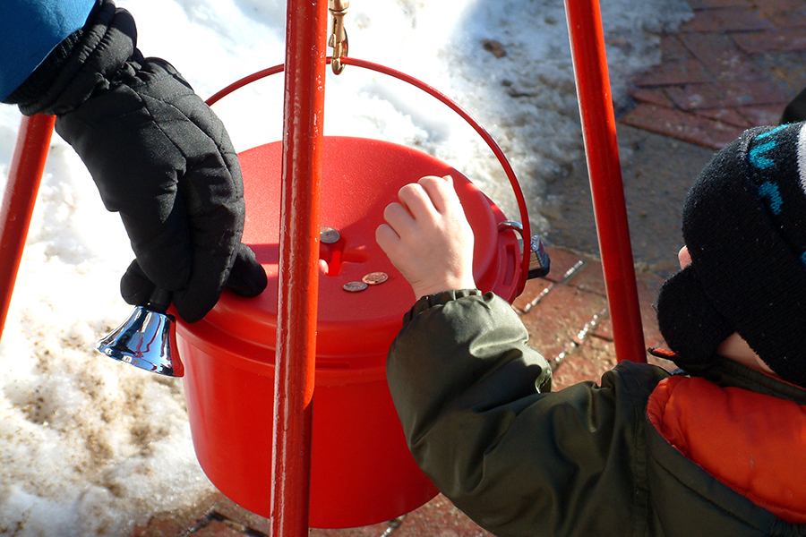 A boy puts coins in a Salvation Army kettle
