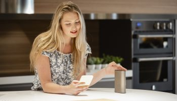 A front-view shot of a young caucasian woman smiling while she uses her smart phone to connect to her virtual assistant smart speaker in her kitchen.