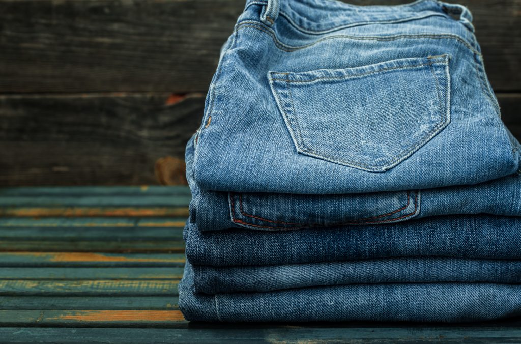bunch of jeans on wooden background, fashionable clothes